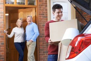 Mum and Dad watching son packing car to leave home