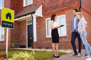 Estate Agent talking to couple outside a house for sale